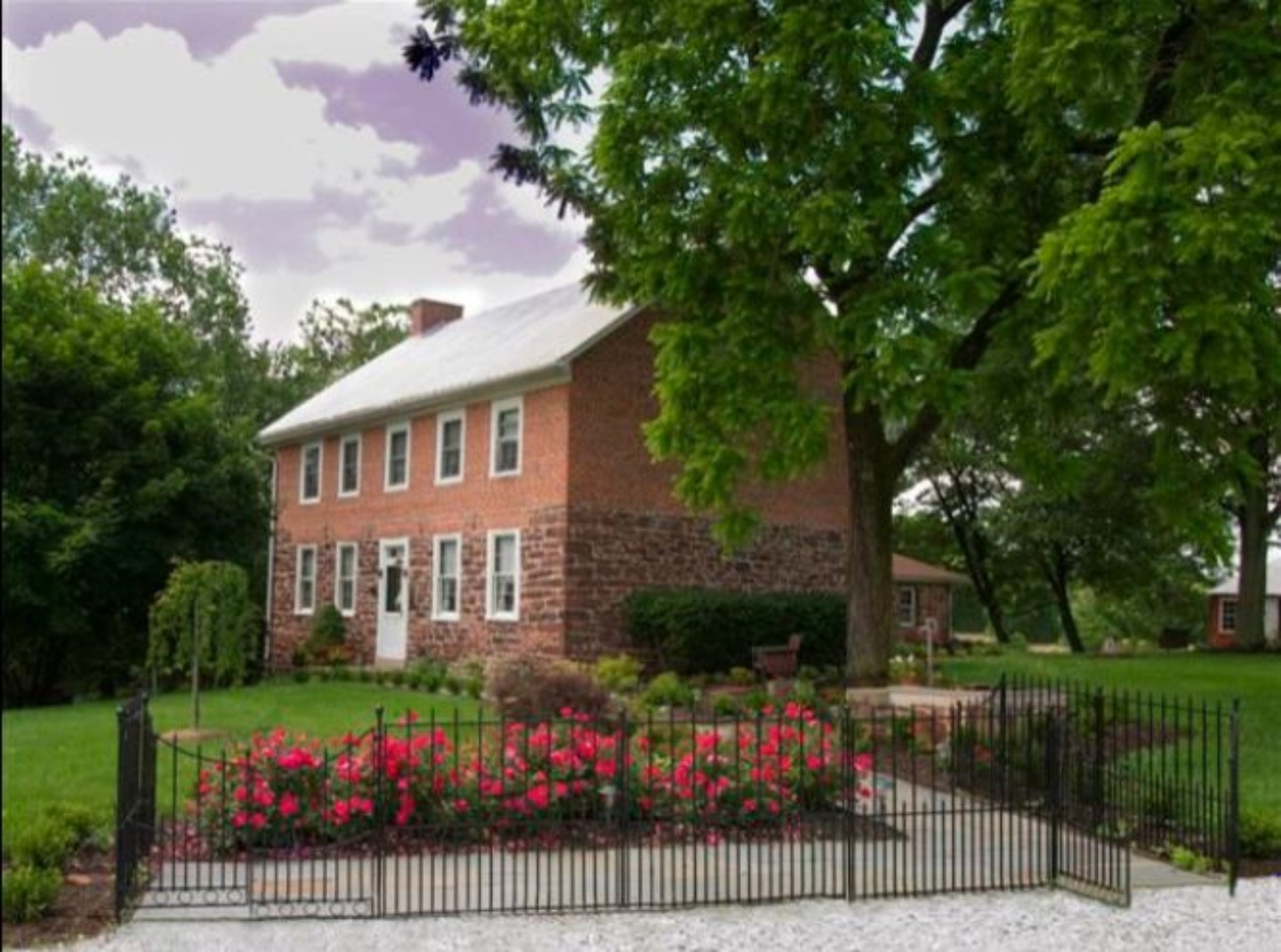 A large brick building with grass in front of a house at Mary-Penn Bed and Breakfast.