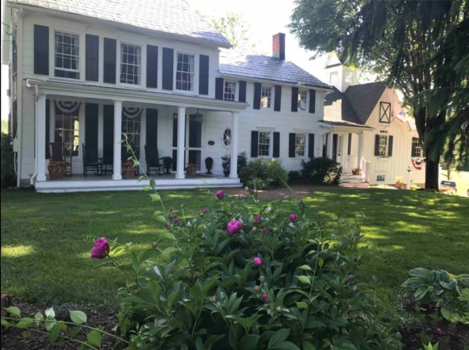 A large lawn in front of a house at Inn at Stony Creek.