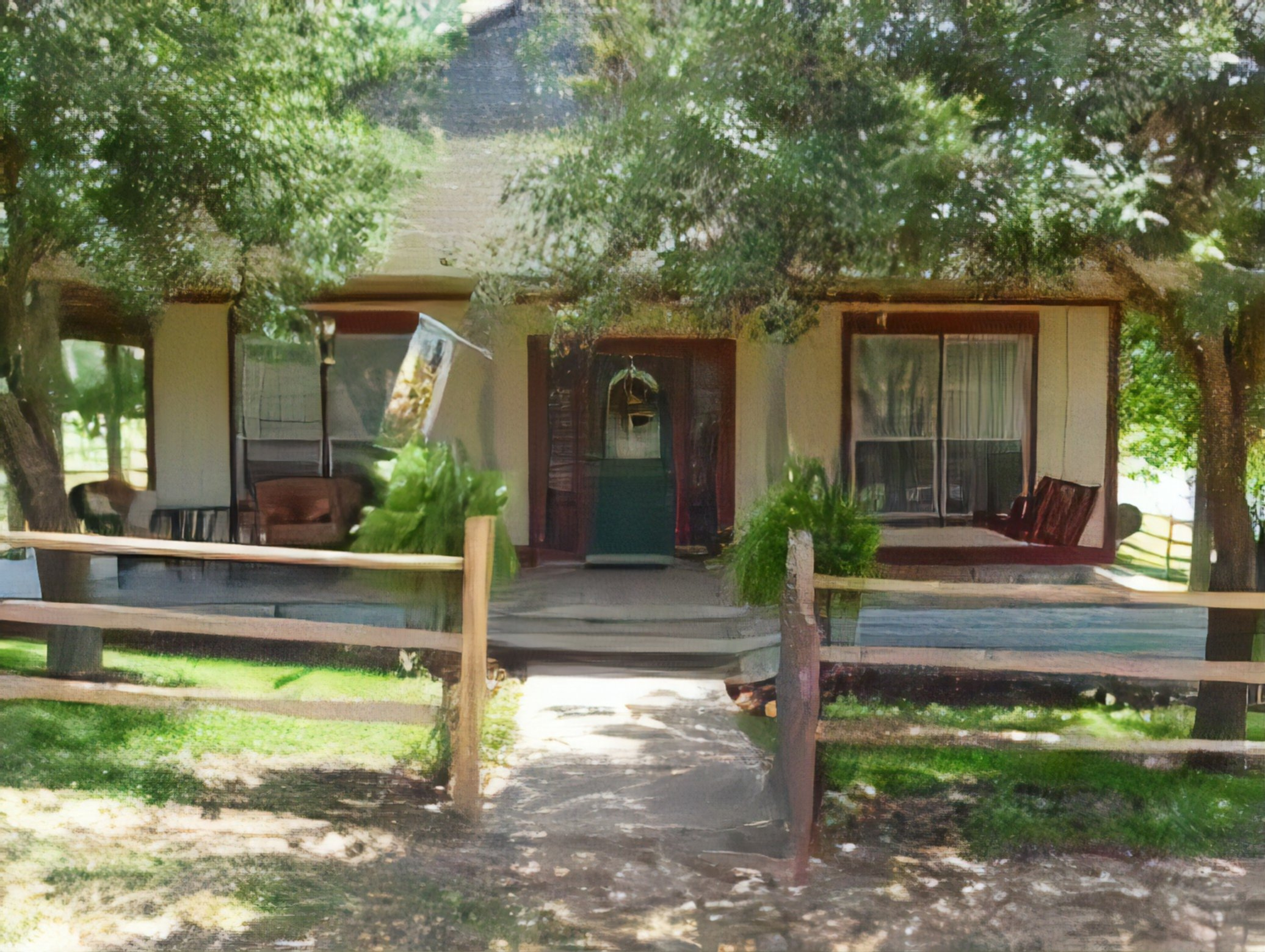 A wooden bench in front of a house at Hackberry Hill Cottages.