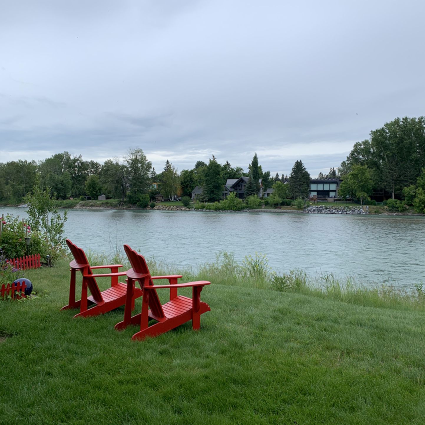 A wooden bench sitting next to a body of water at Along River Ridge Bed and Breakfast.