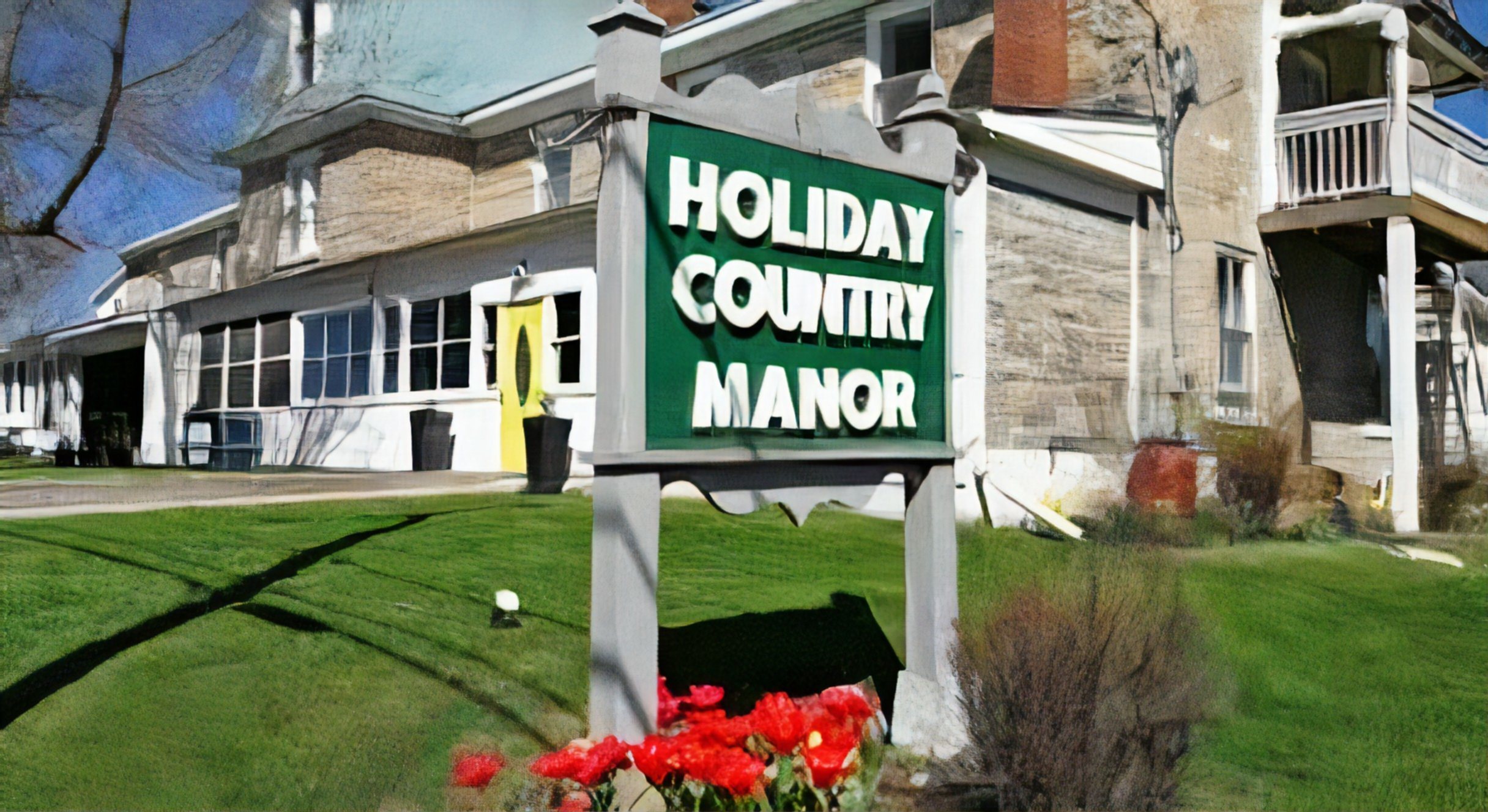A sign in front of a building at Holiday Country Manor .