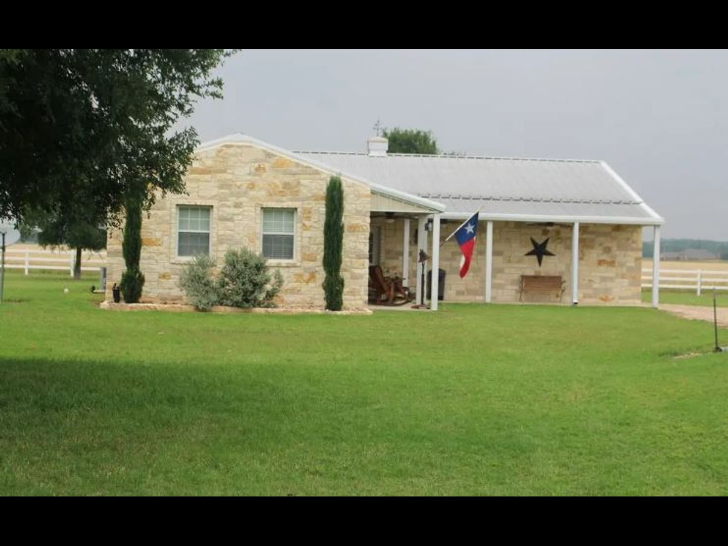 A house with a grass field at Texas Star Bed & Breakfast.