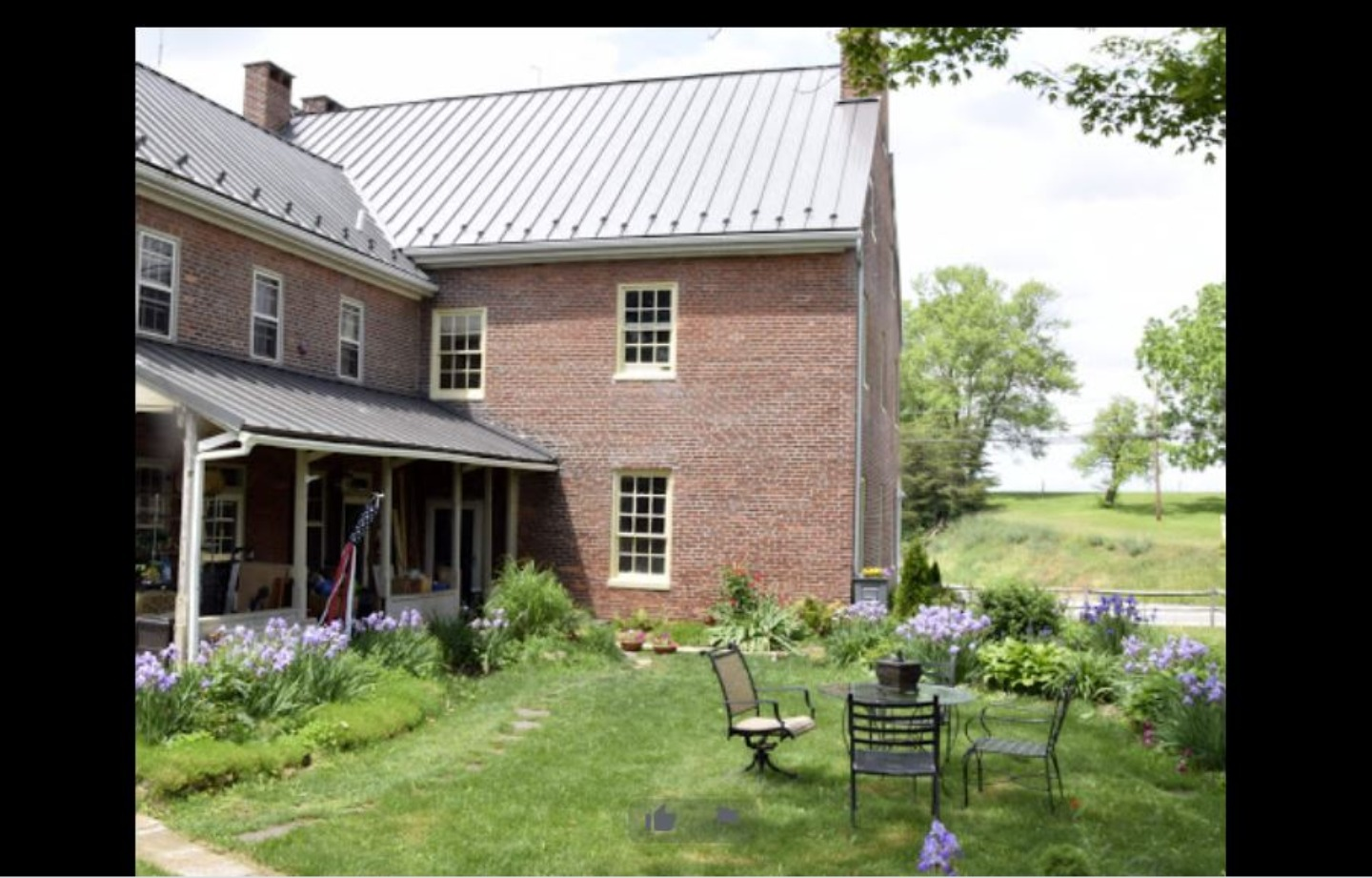 A large brick building with grass in front of a house at The 1788 Inn.