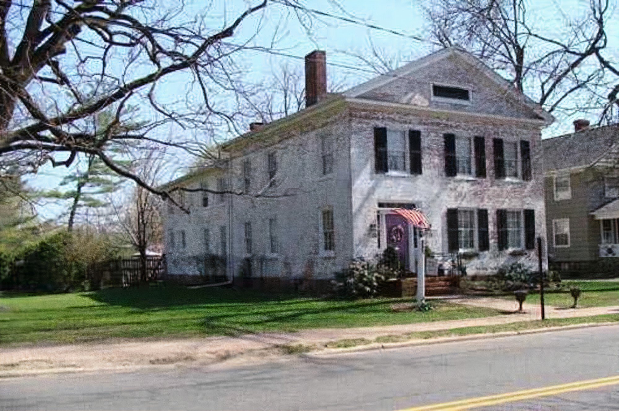 A large brick building with grass in front of a house at Chez Lafayette Bed & Breakfast.