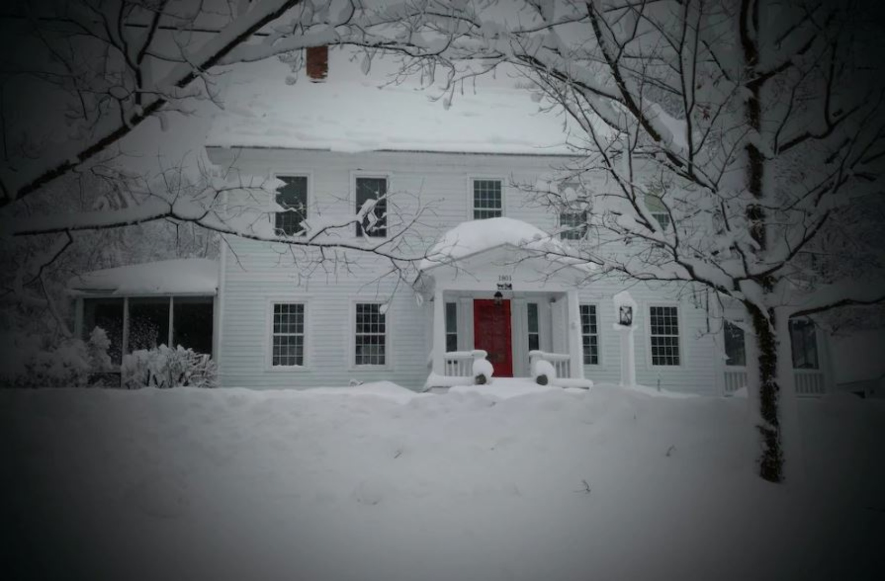 A house covered in snow at Buckmaster Inn Bed and Breakfast.
