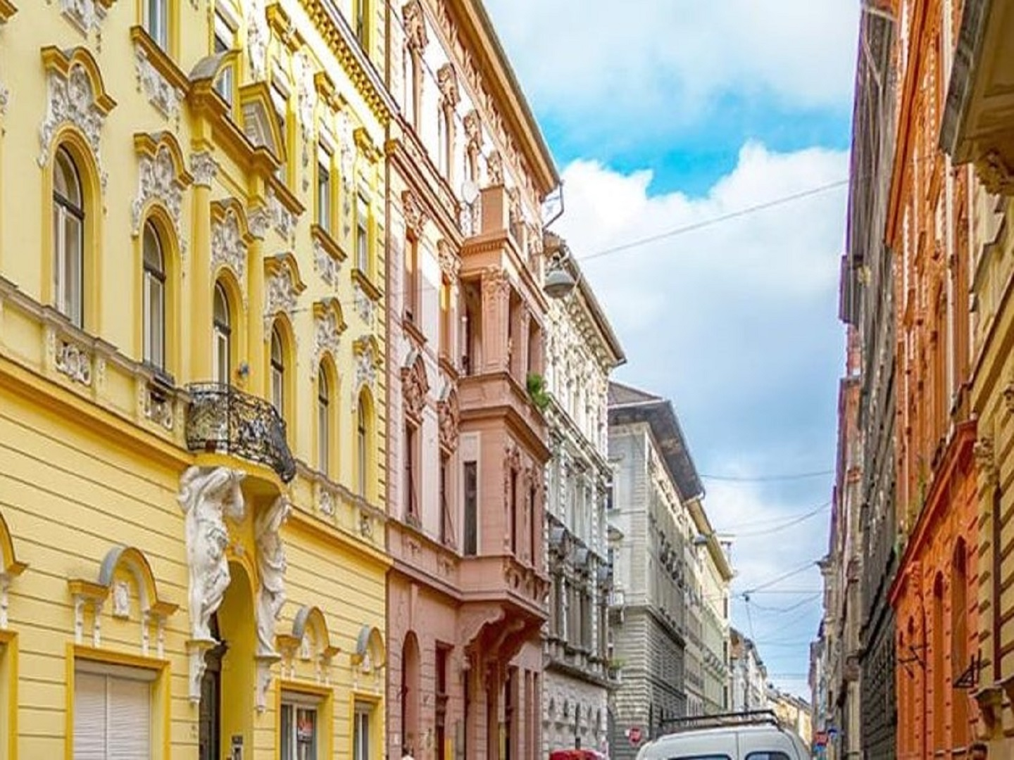 A narrow city street with buildings on the side of a building at Kapital Inn Budapest.