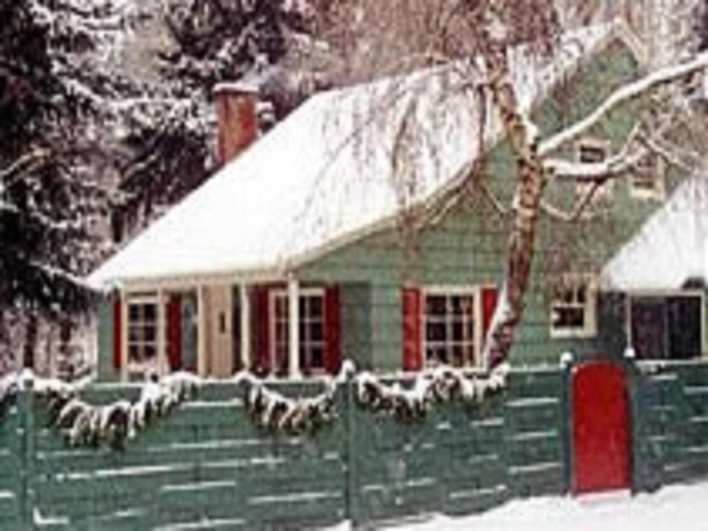 A house with trees in the background at Kelly's Trout Creek Inn Bed.