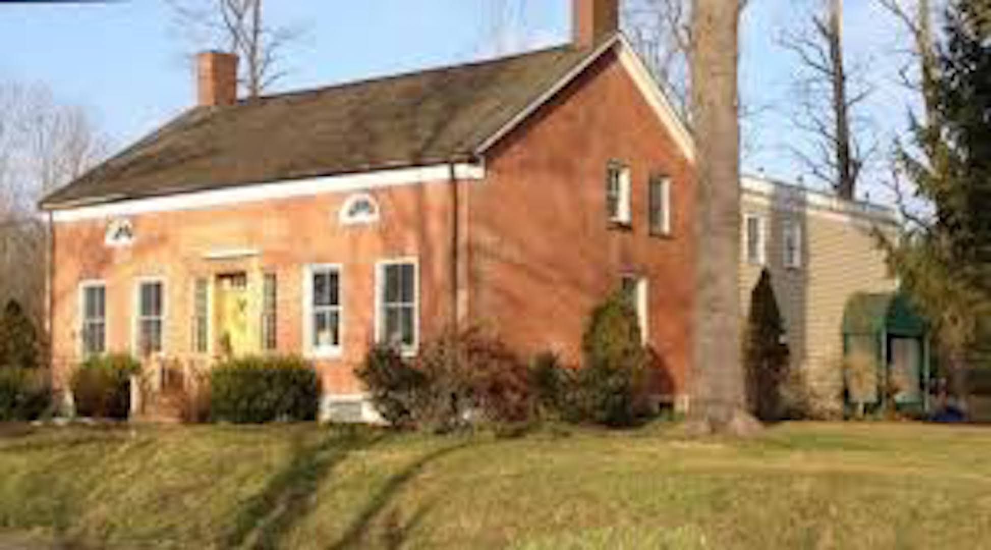 A large brick building with grass in front of a house at Elm Rock Inn B&B.