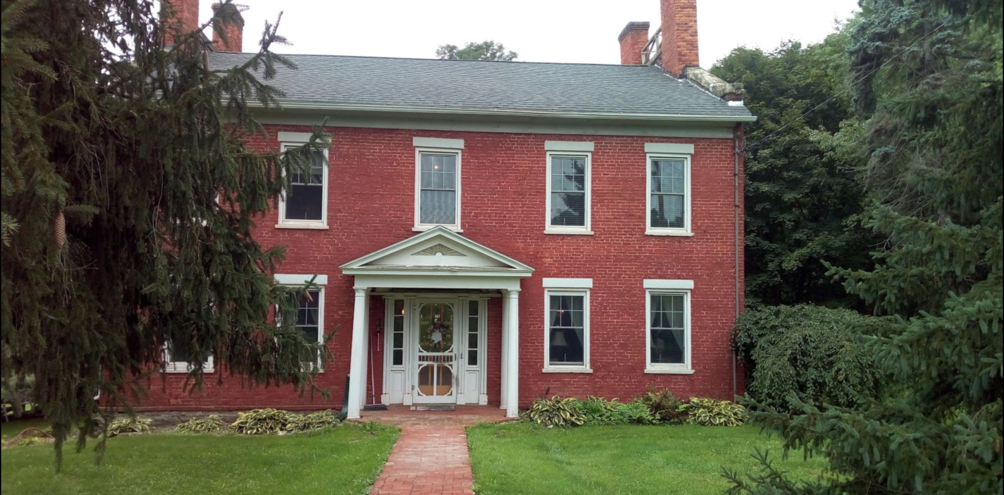 A large brick building with grass in front of a house at 1819 Red Brick Inn.