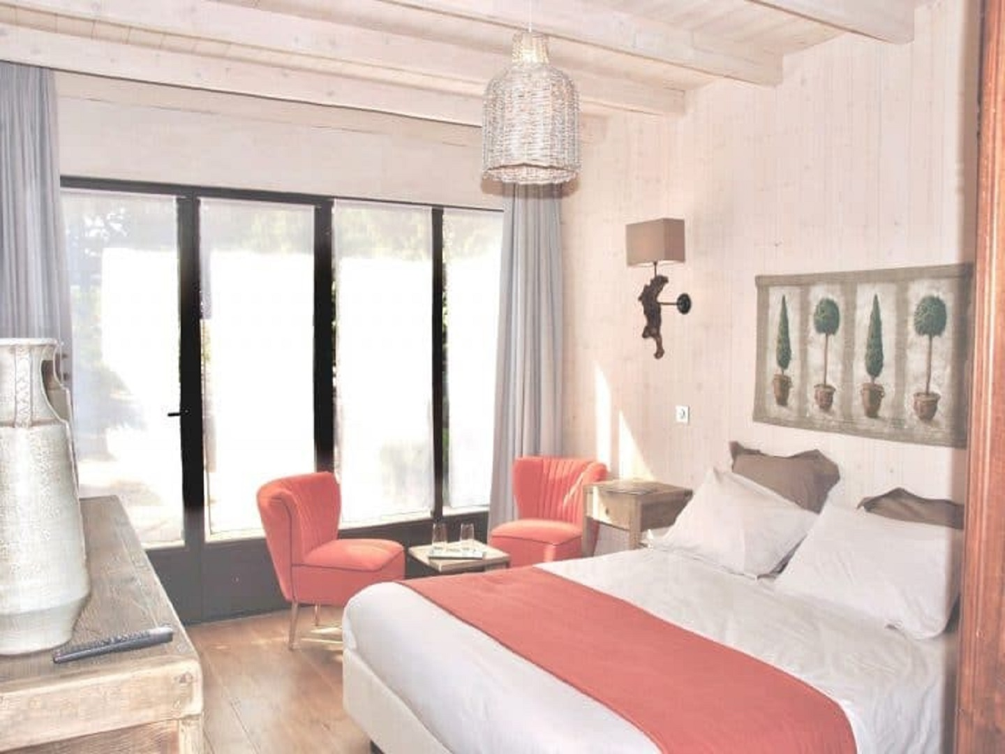 A bedroom with a large window at La Bastide aux Bois.