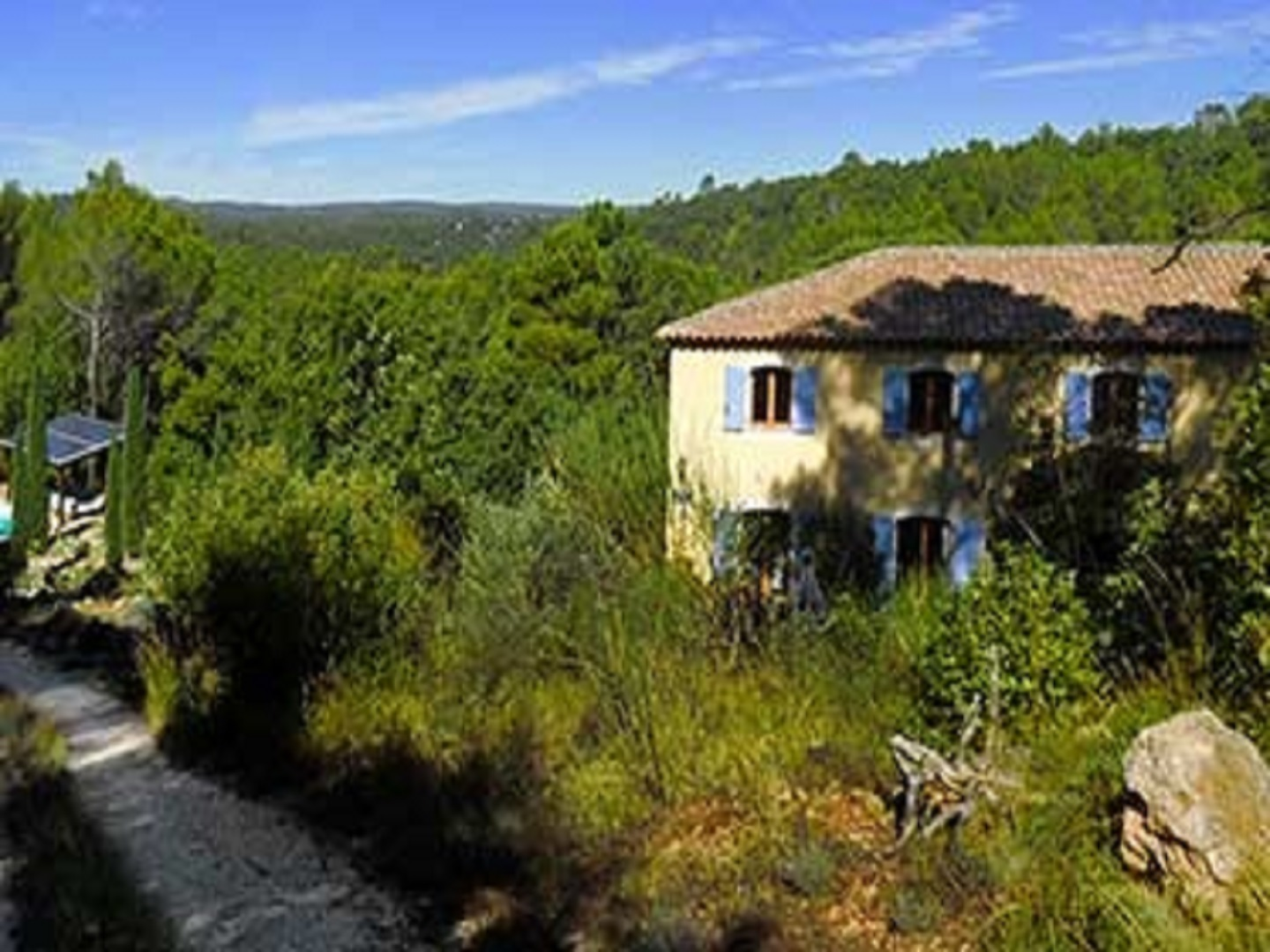 A house with trees in the background at La Bastide des Templiers en Provence .