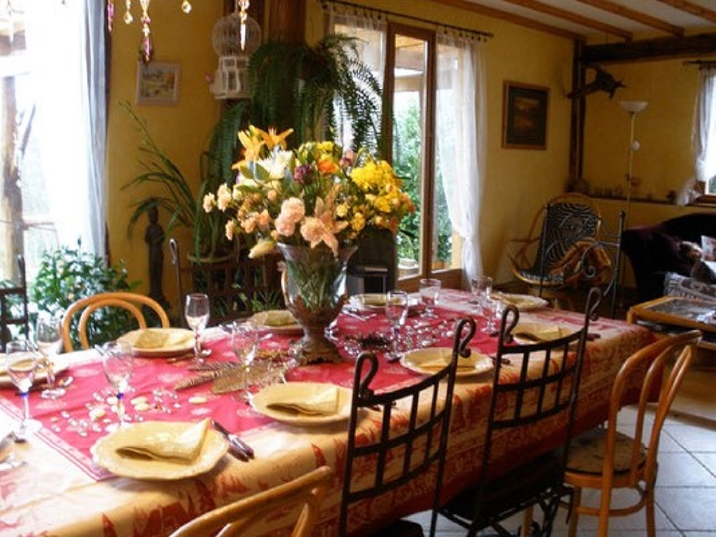 A room filled with furniture and vase of flowers on a table at La grange du rossignolet.