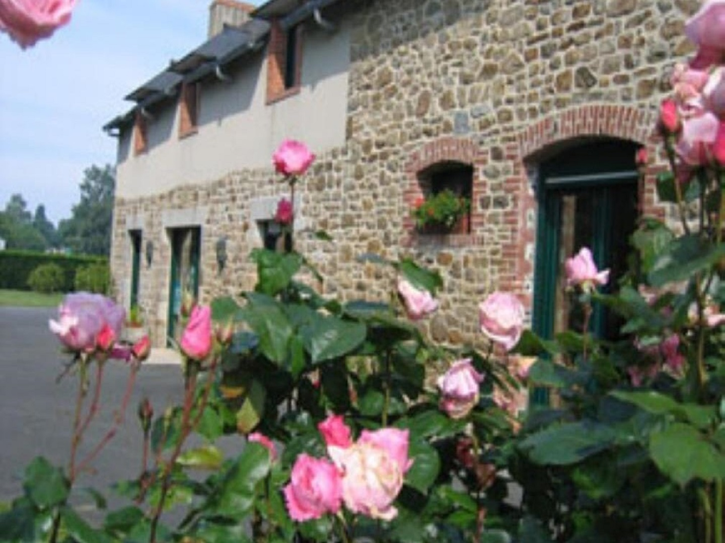 A pink flower is standing in front of a building at La Jacotière .