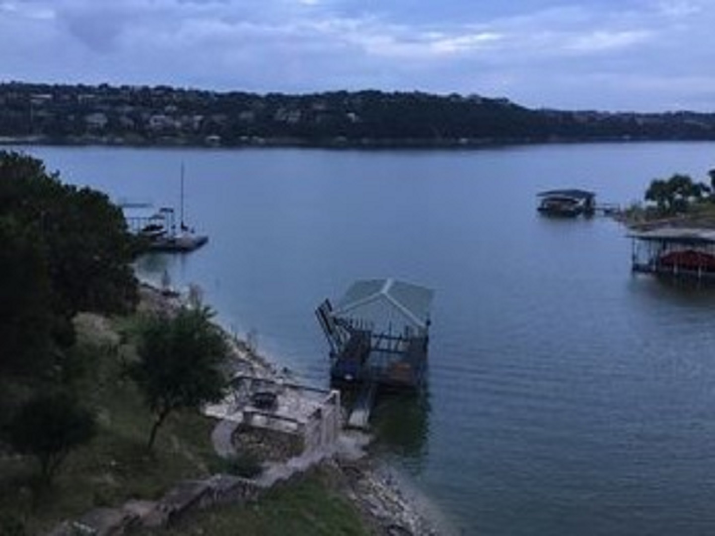 A small boat in a large body of water at Lake Travis Cozy Cove Vacation Cottage Rentals.