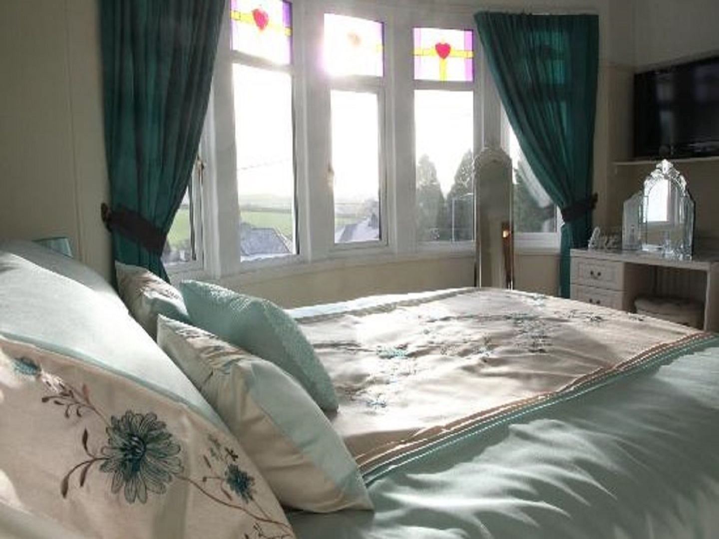 A bedroom with a bed and a window at Langdale House.