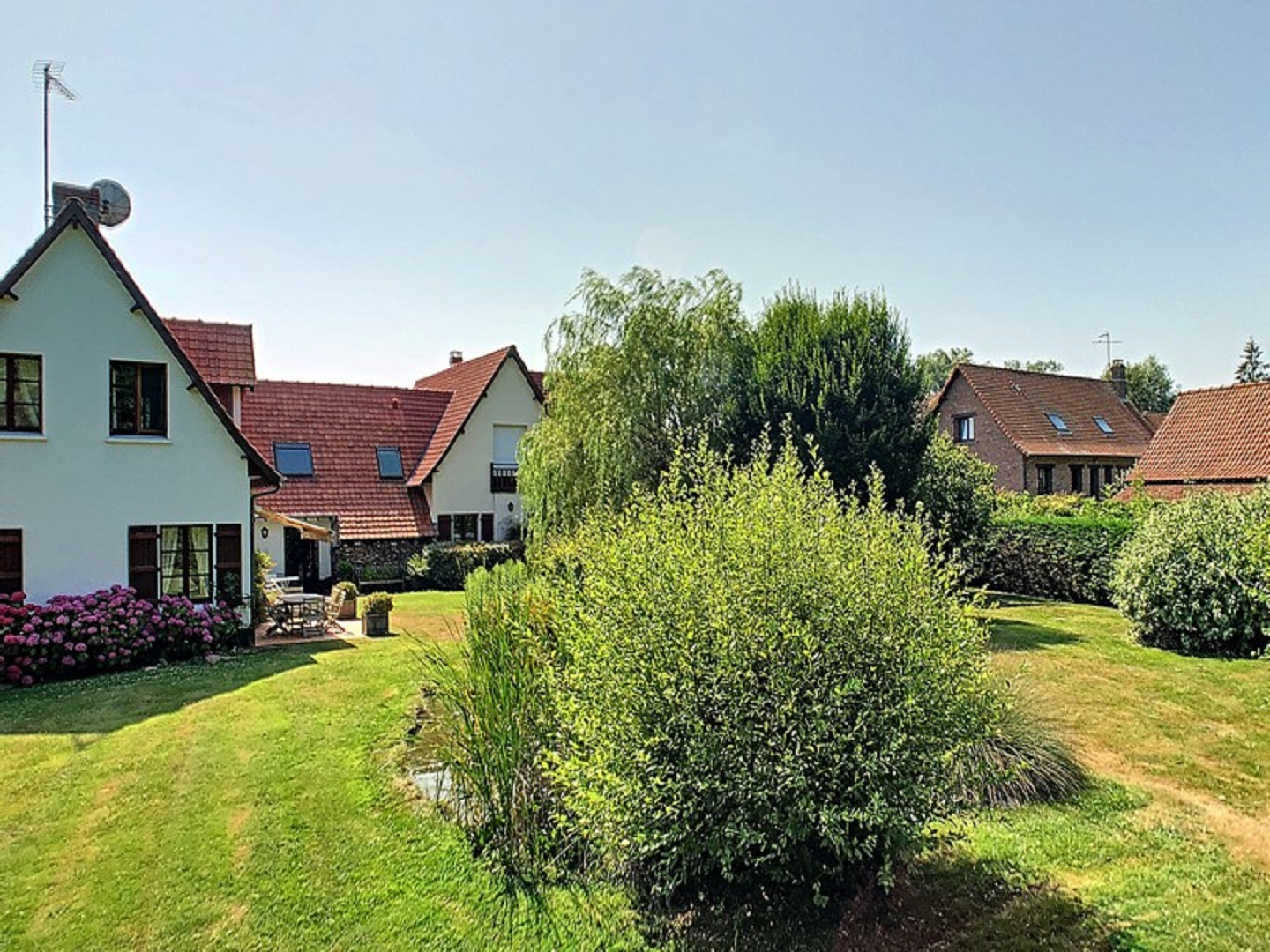 A large brick building with green grass in front of a house at Le Clos de l'Ermitage.