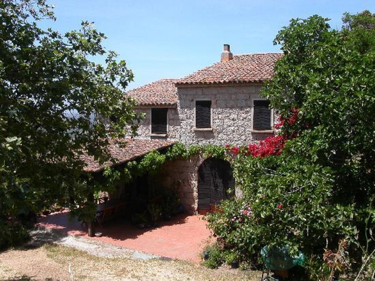 A house with bushes in front of a brick building at Le Domaine de Croccano.