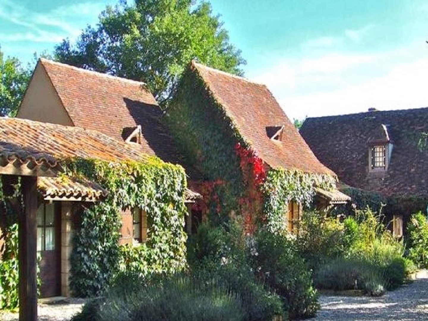 An old brick house with trees in the background at Le Domaine de La Millasserie.