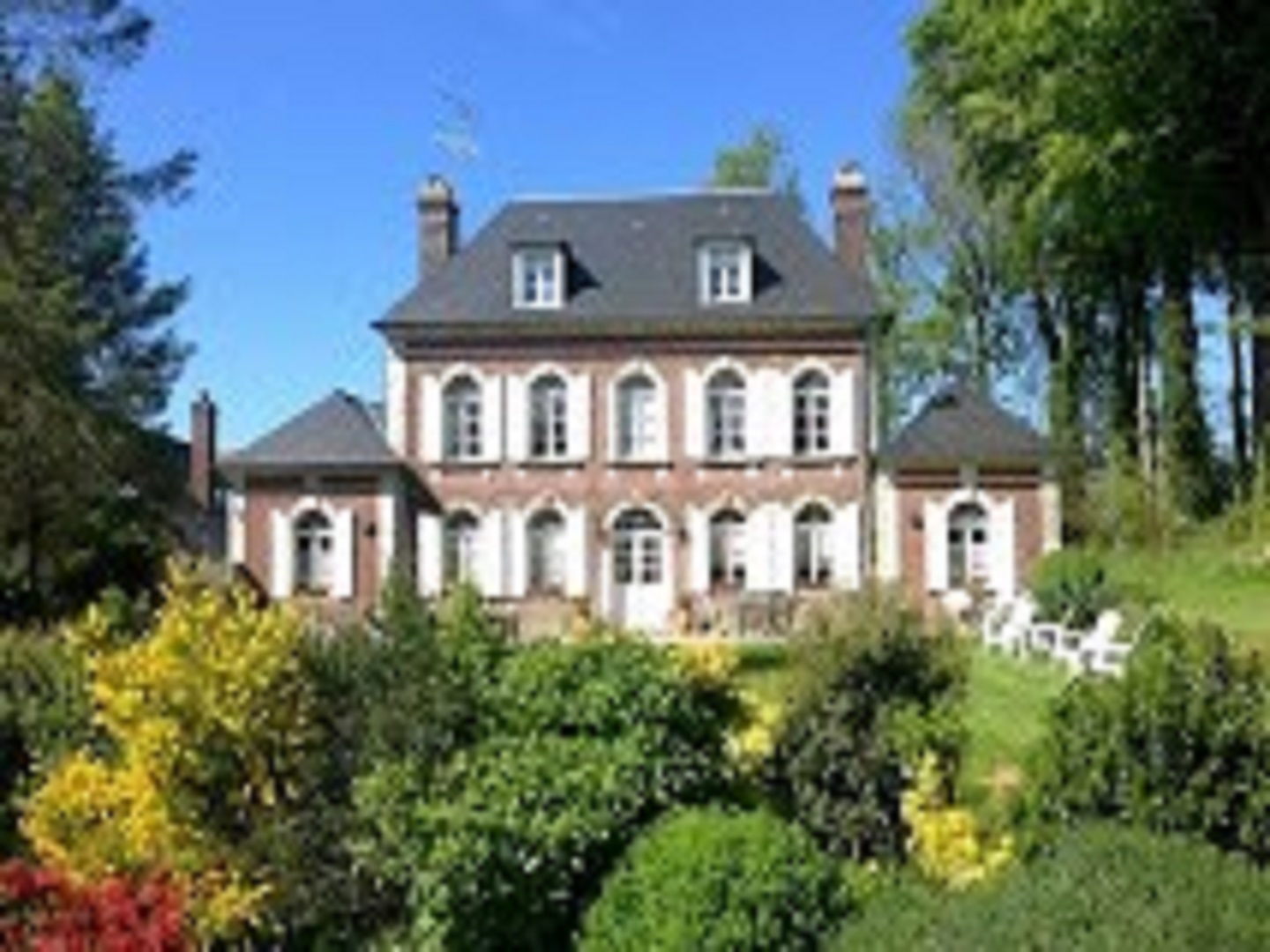 A house with bushes in front of a building at Le domaine de Vaux.
