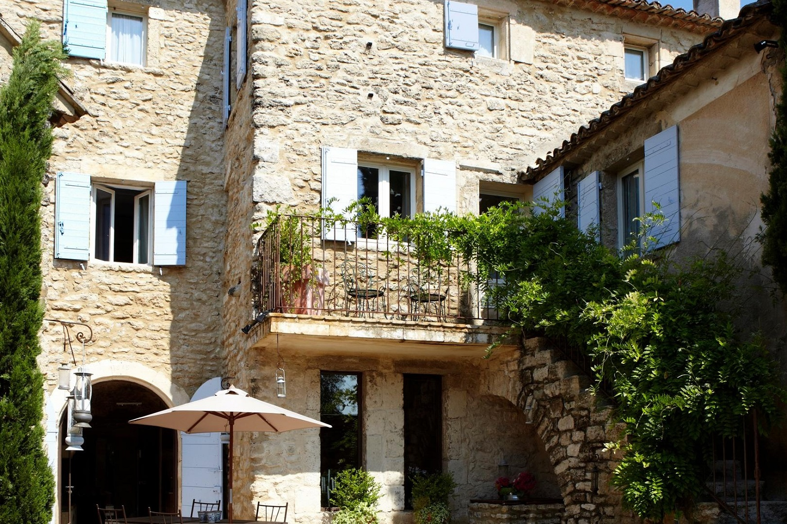 A stone building that has a bench in front of a house at Le nid de rochefort.