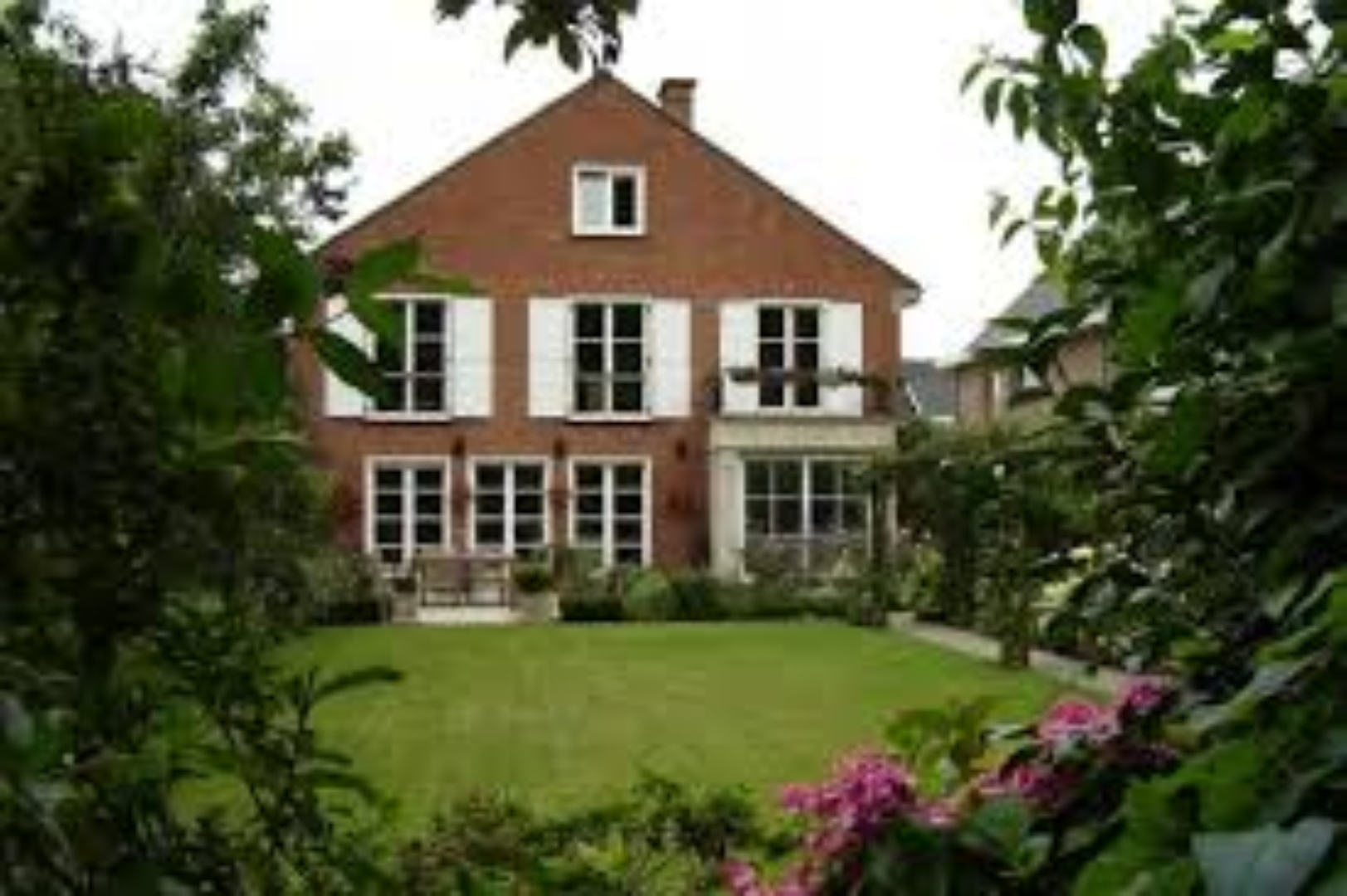 A large brick building with grass in front of a house at Brugge-man Bed and Breakfast, Chambres d'hôtes.