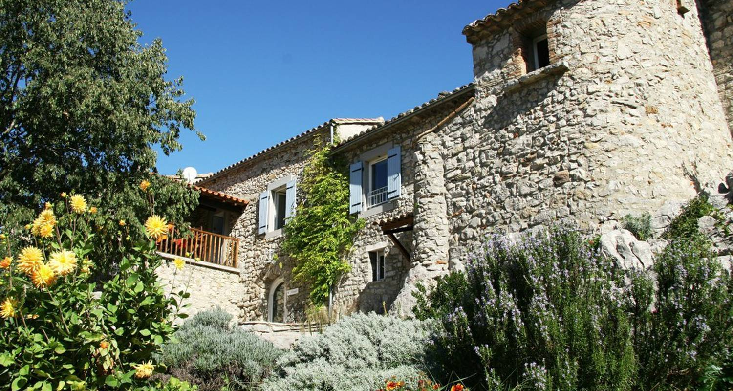 A house with bushes in front of a brick building at Les Hauts d'issensac.