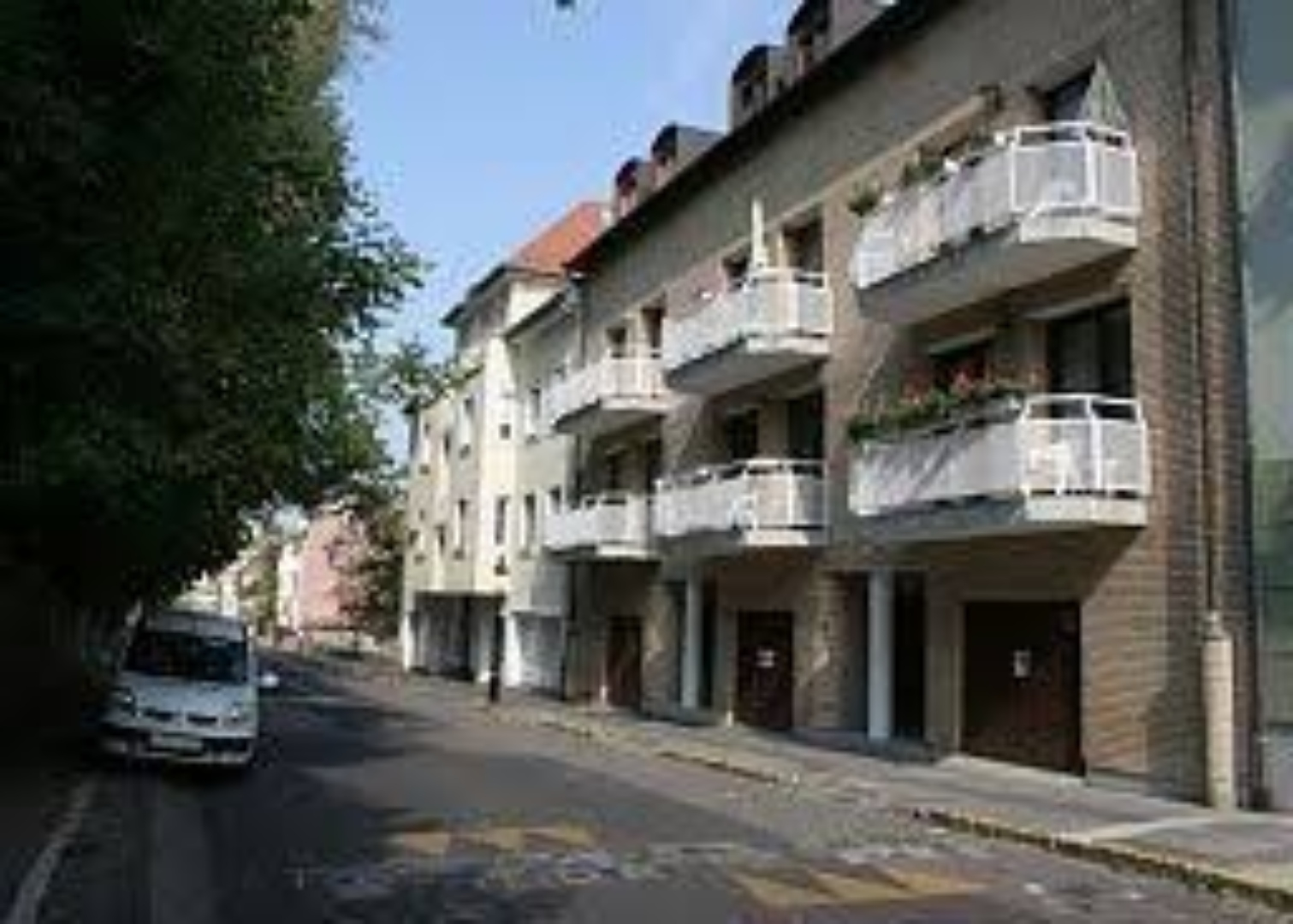 A narrow city street with cars parked on the side of a building at Budavar Pension B&B.