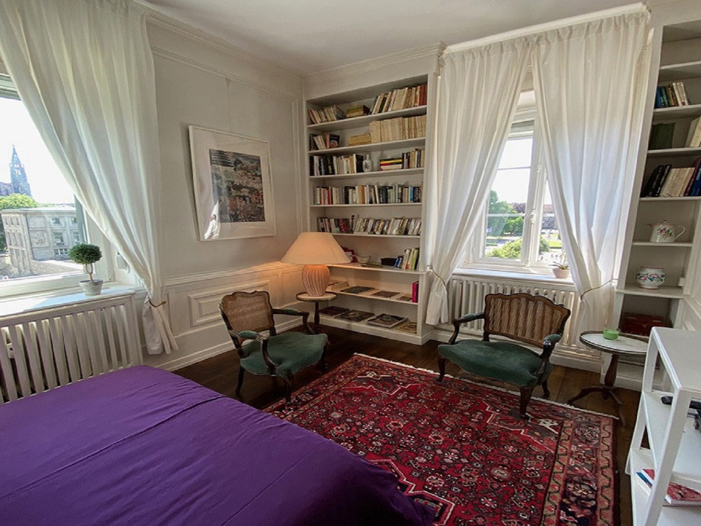 A bedroom with a bed and a chair in a room at LES LUMIERES DE LA VILLE.