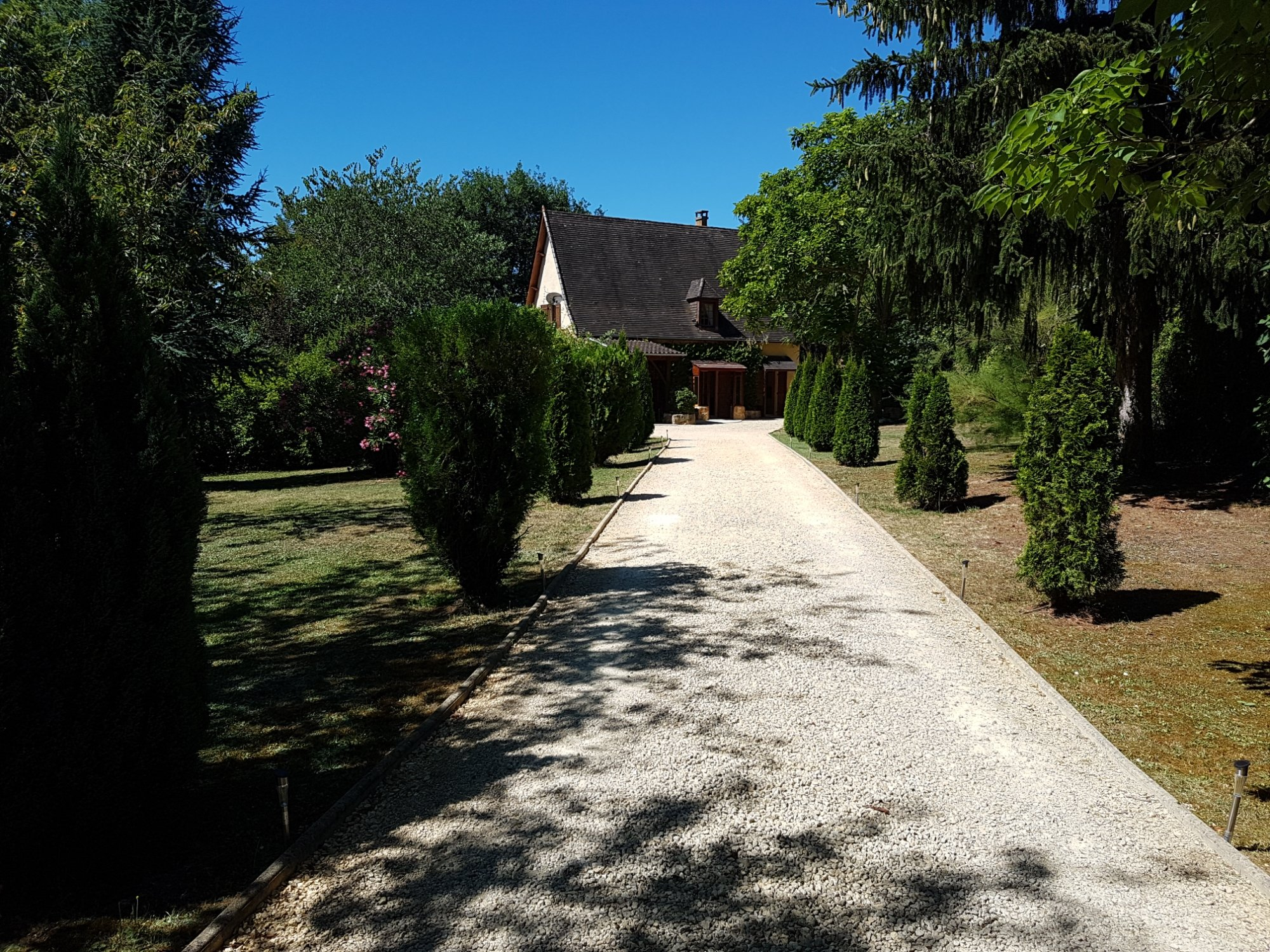 A path with trees on the side of a house at Les plantous de Severo - Espace bien être.
