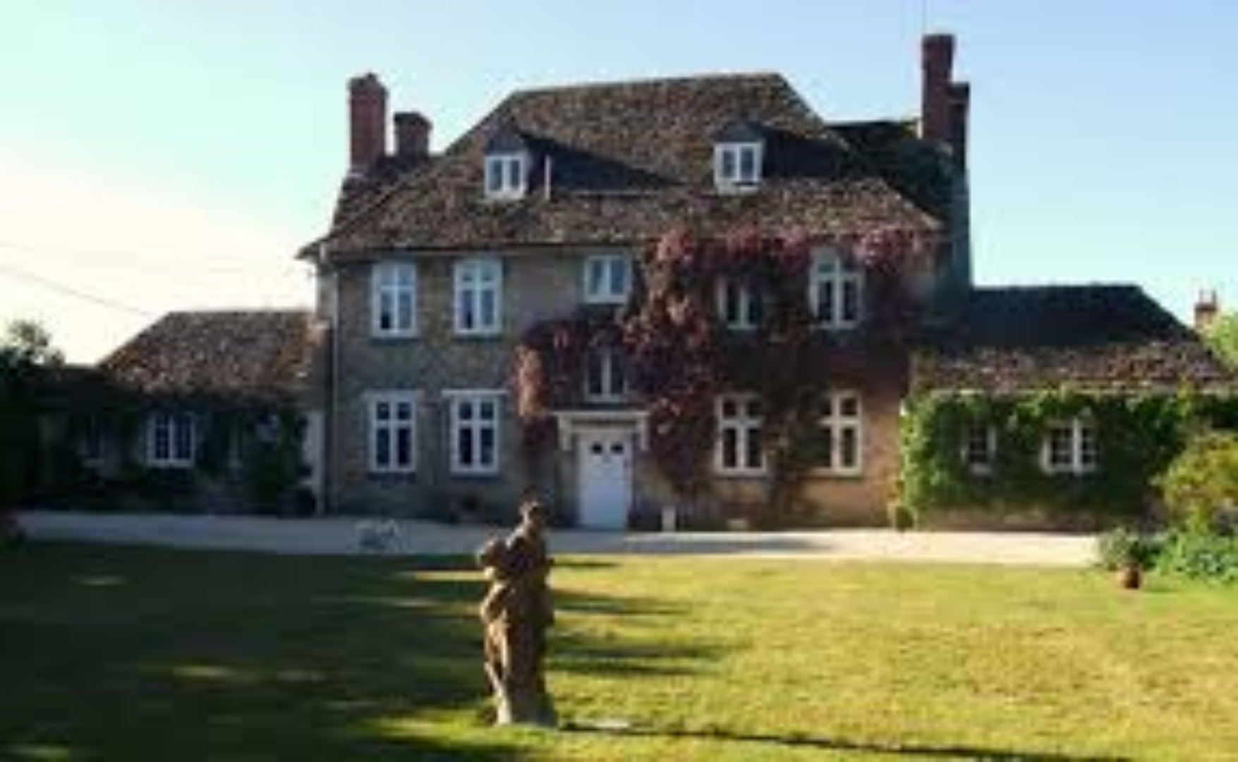 A large brick building with grass in front of a house at Buscot Manor.