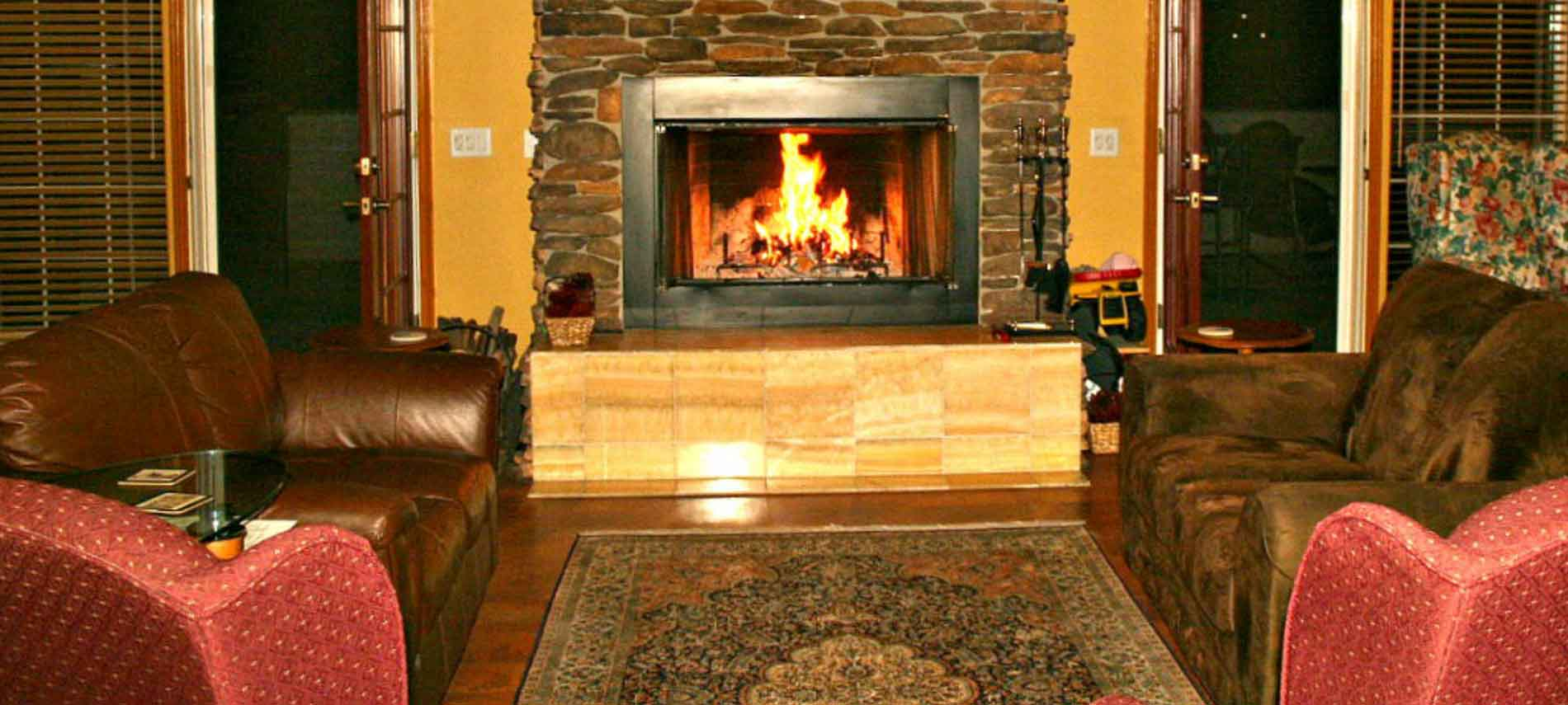 A fire place sitting in a living room filled with furniture and a fireplace at Lucinda's Country Inn.