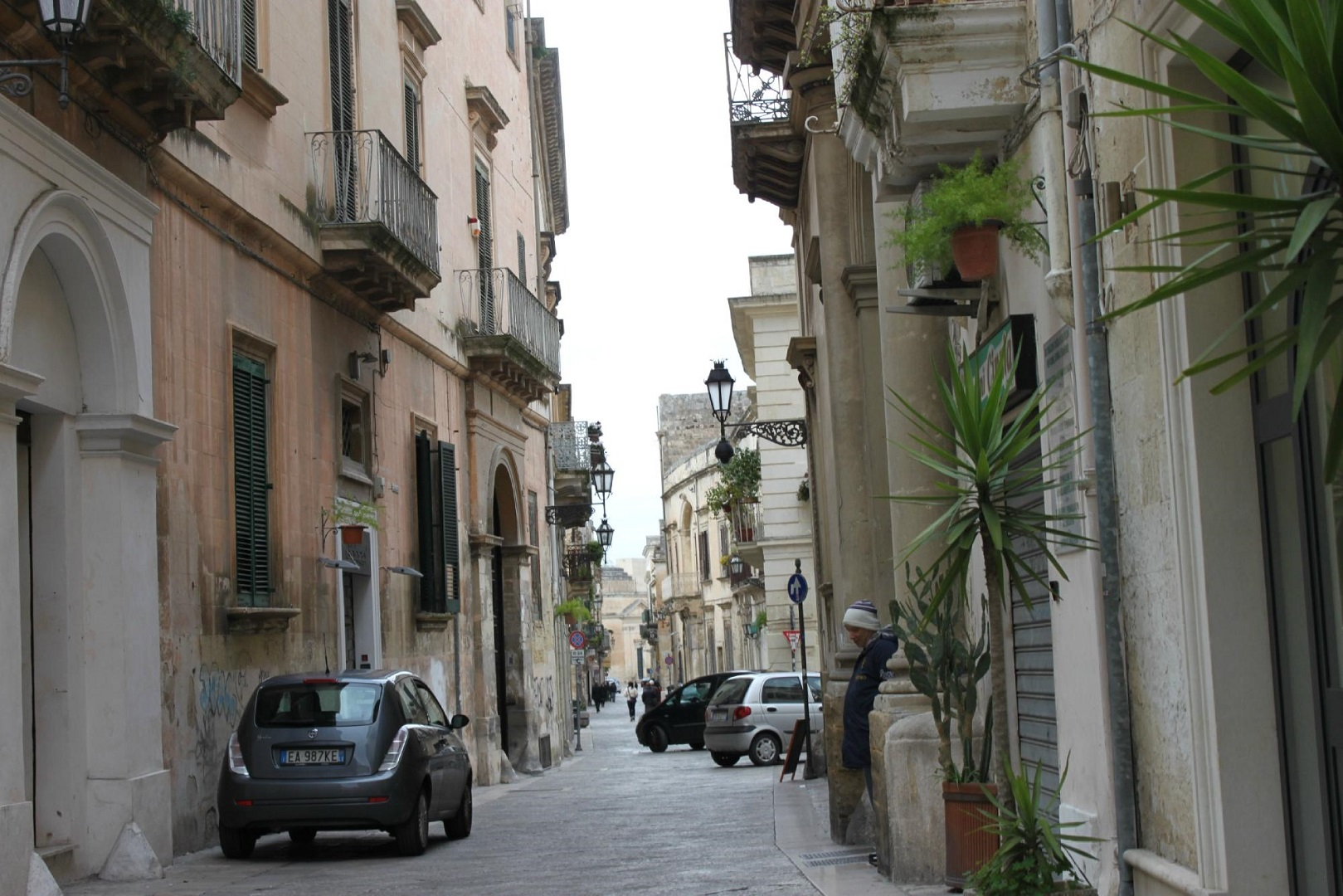 A narrow city street with cars parked on the side of a building at LUNA PIENA.