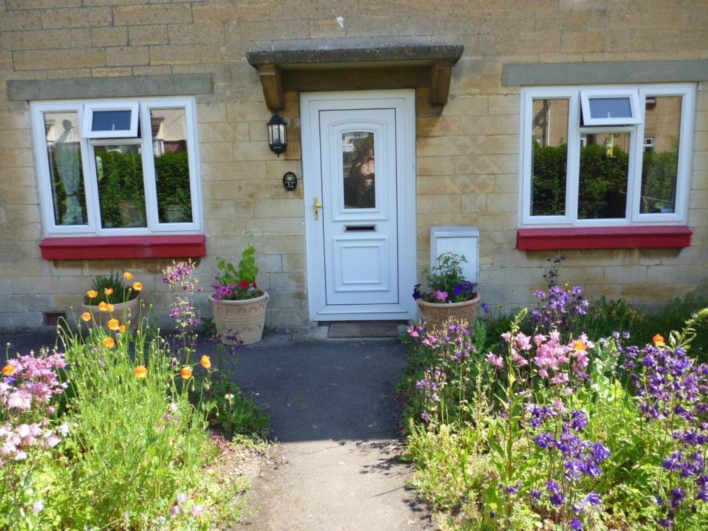 A close up of a flower garden in front of a house at Calne Bed and Breakfast.