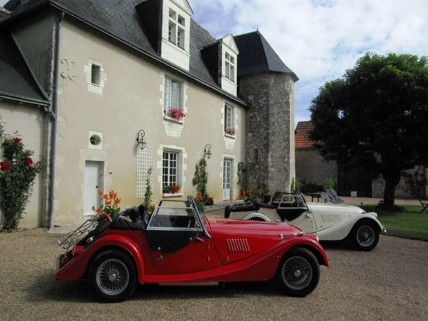 A car parked in front of a house at Manoir de Chaix.