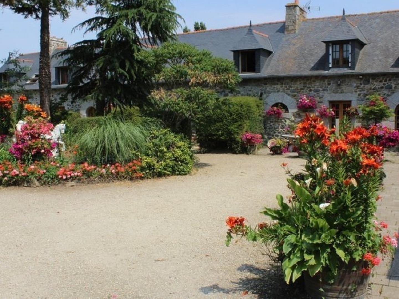 A close up of a flower garden in front of a building at Manoir de la Fontaine Ménard.