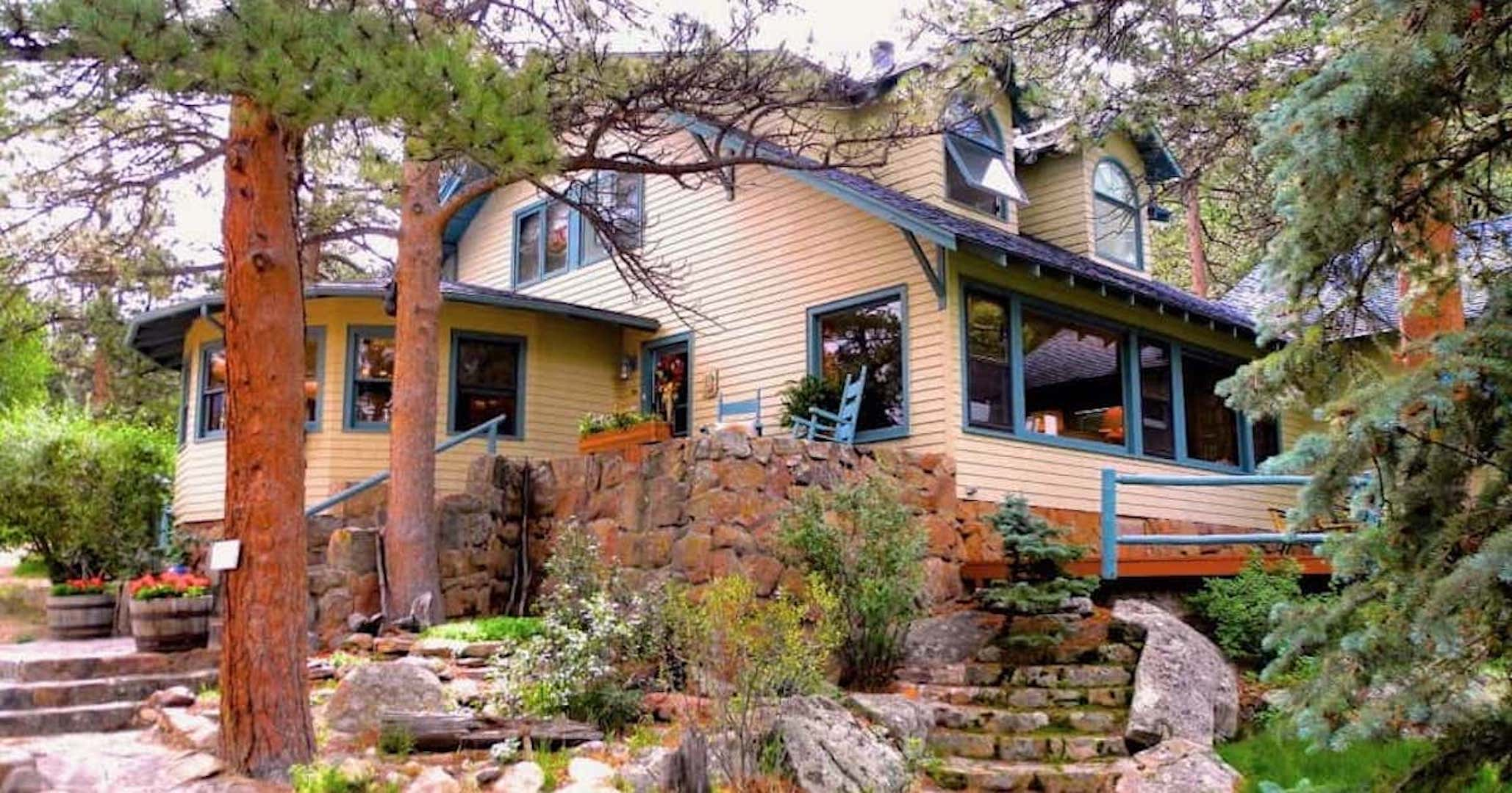 A tree in front of a house at Estes Park Bed and Breakfast.