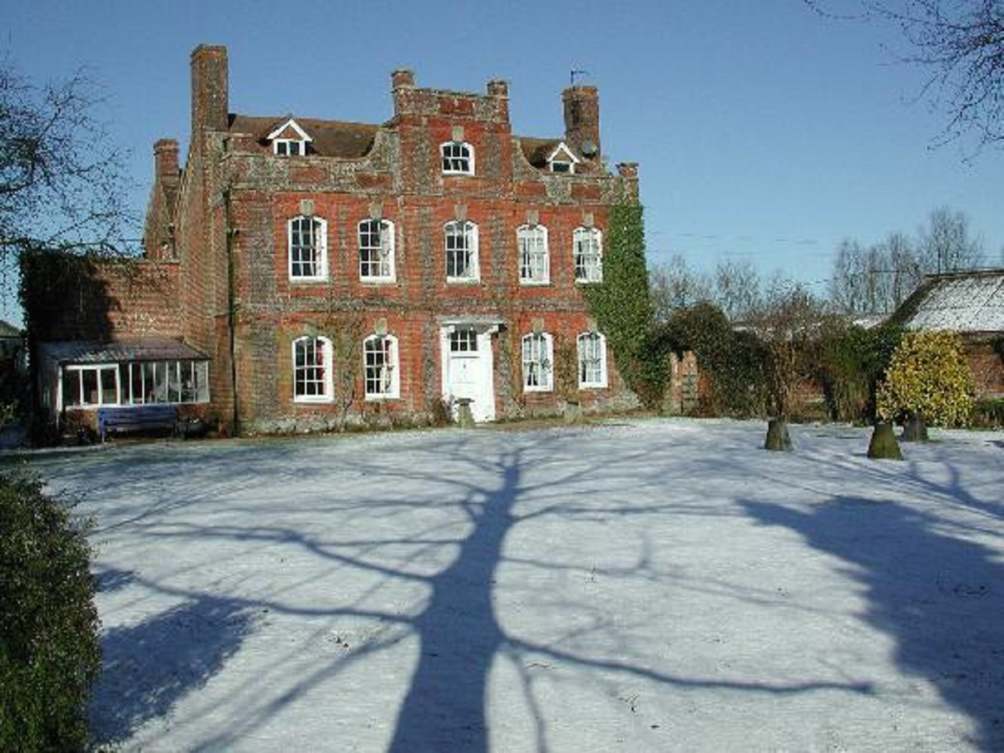 A house covered in snow in front of a brick building at Manor Farm B & B.