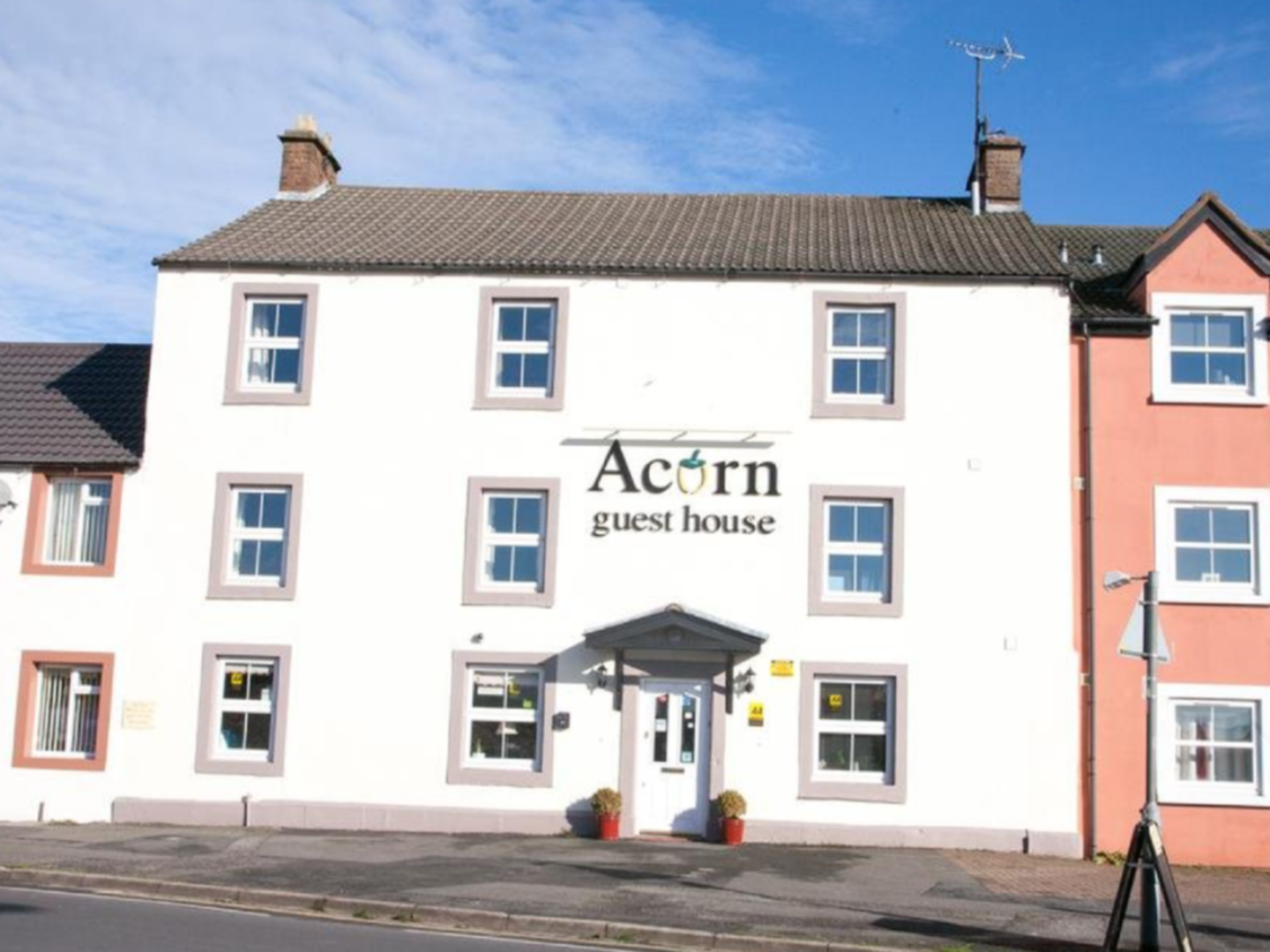 A house that is parked on the side of a building at Acorn Guest House.