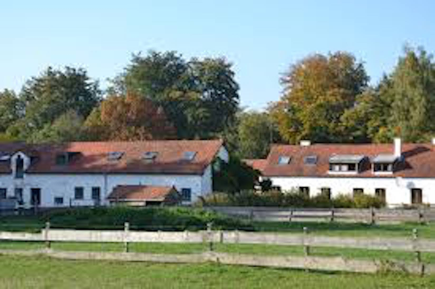 A house with trees in the background at Ferme De La Houlotte.
