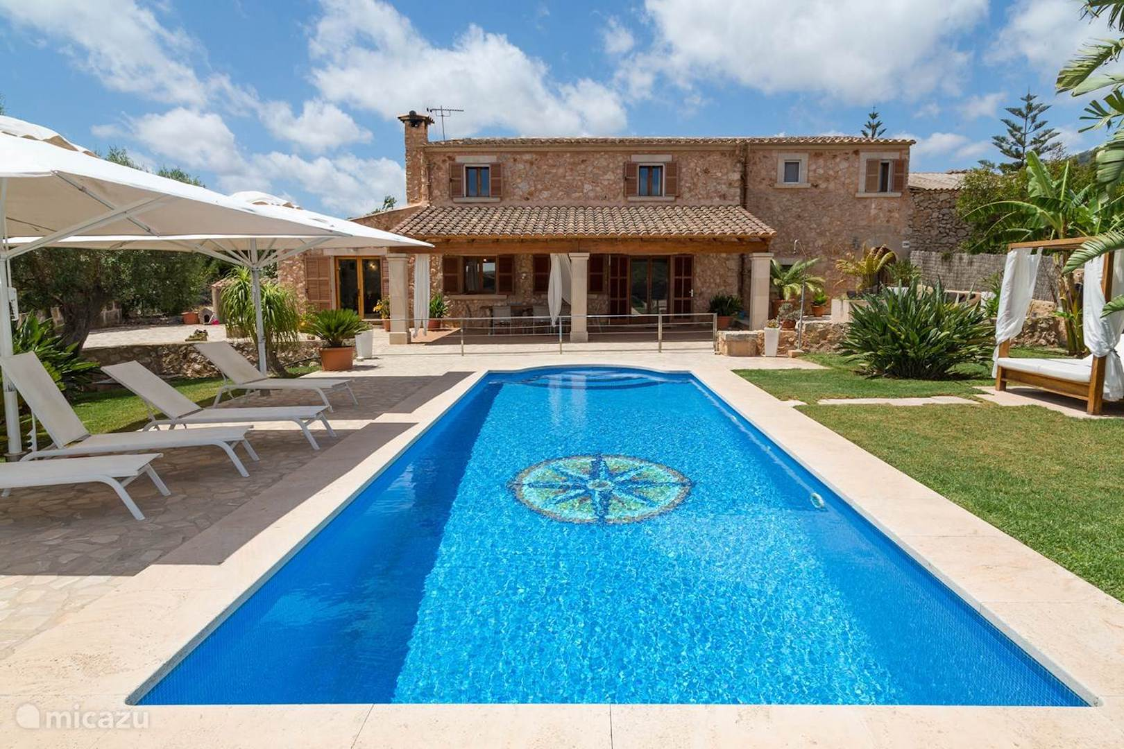 A house with a pool in front of a building at Finca David.
