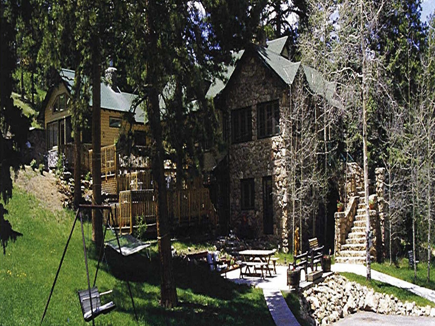 A house with trees in the background at Meadow Creek Mountain Lodge and Event center.