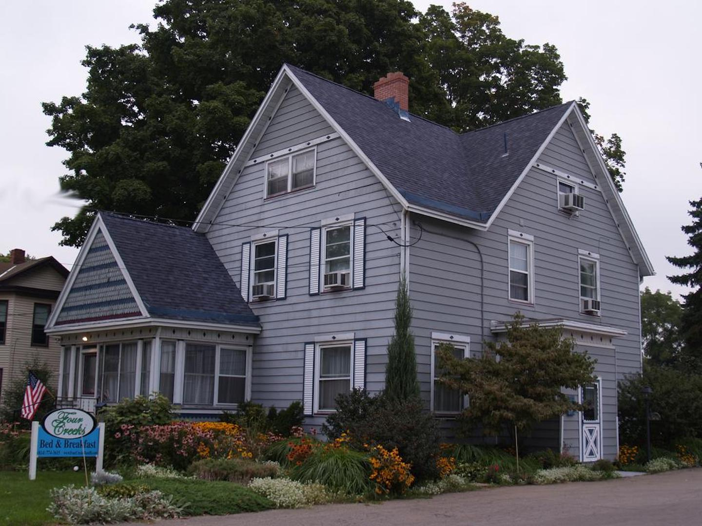 A house in front of a building at Four Creeks Bed & Breakfast.