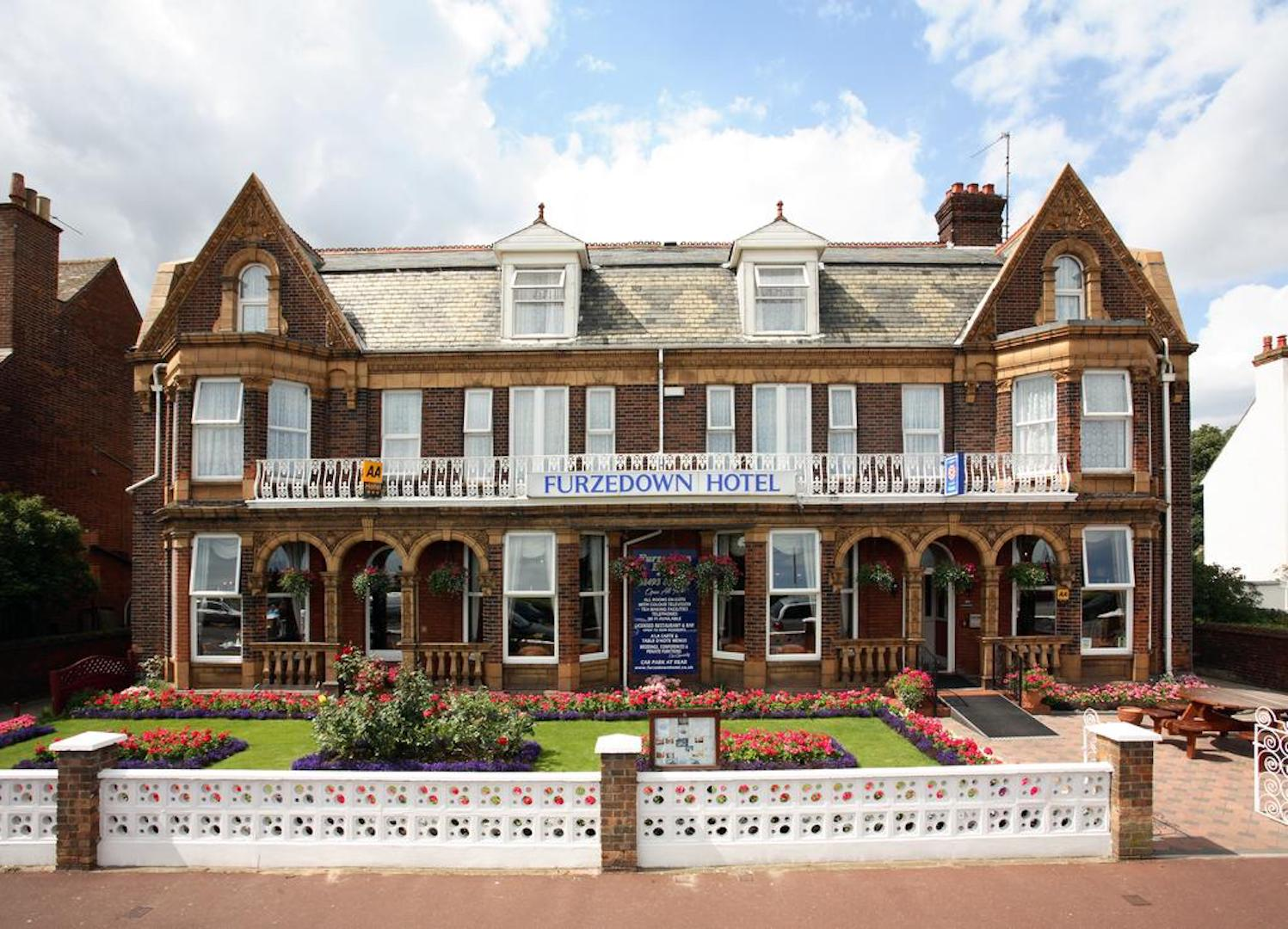 A large brick building with grass in front of a house at Furzedown Hotel.