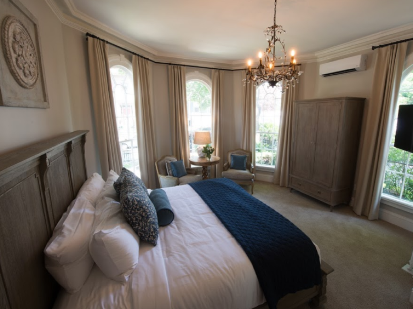 A bedroom with a bed and a chair in front of a window at Adele Turner Inn.