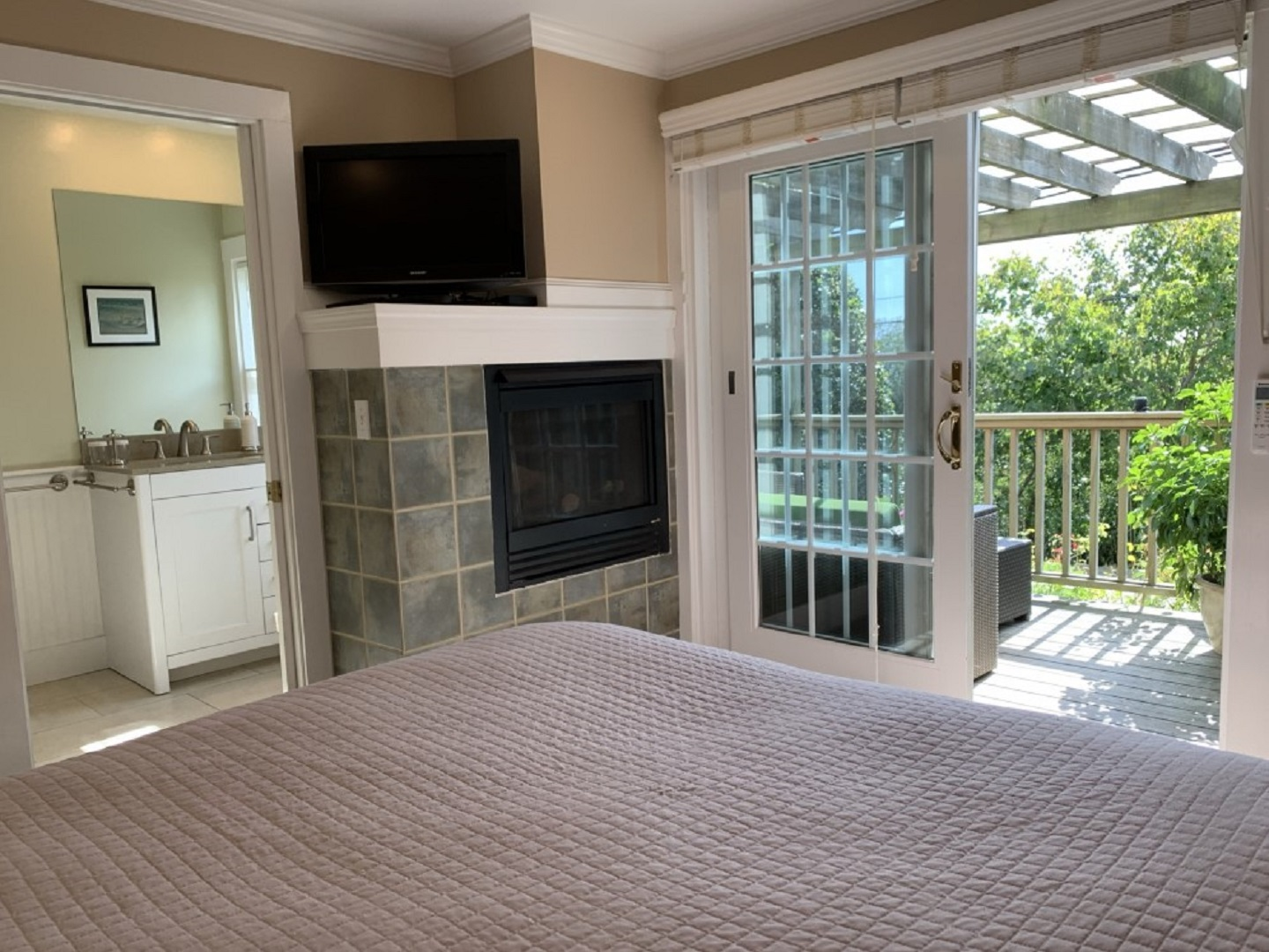 A living room with a fireplace and a large window at Aerie House & Beach Club.