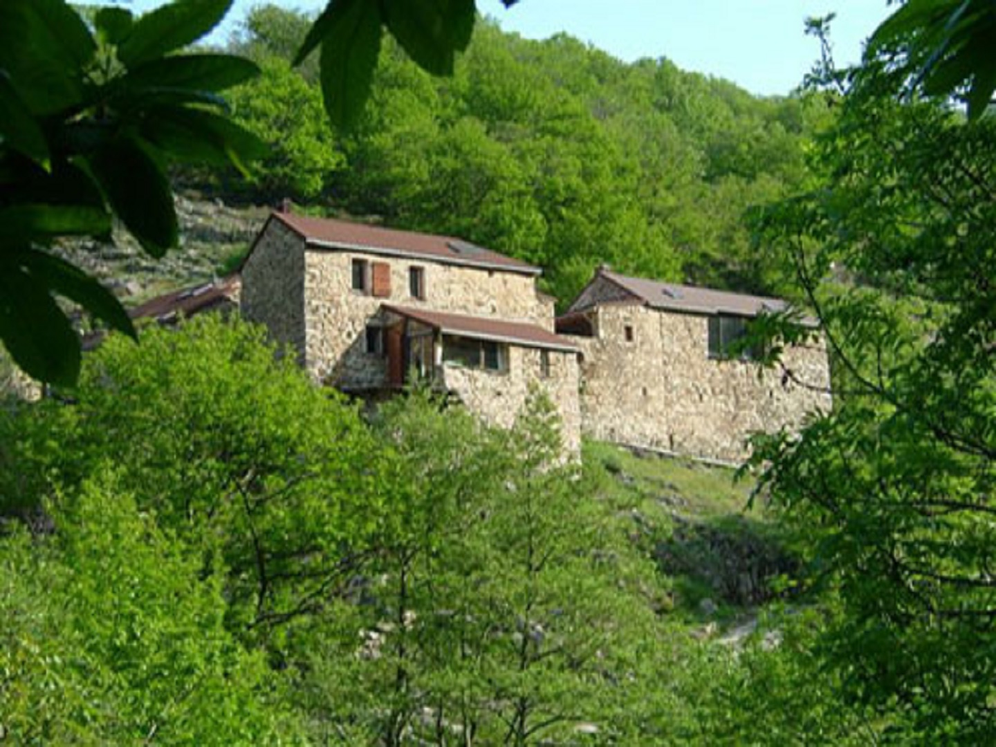 A house with bushes in the background at Moulin Deleuze.