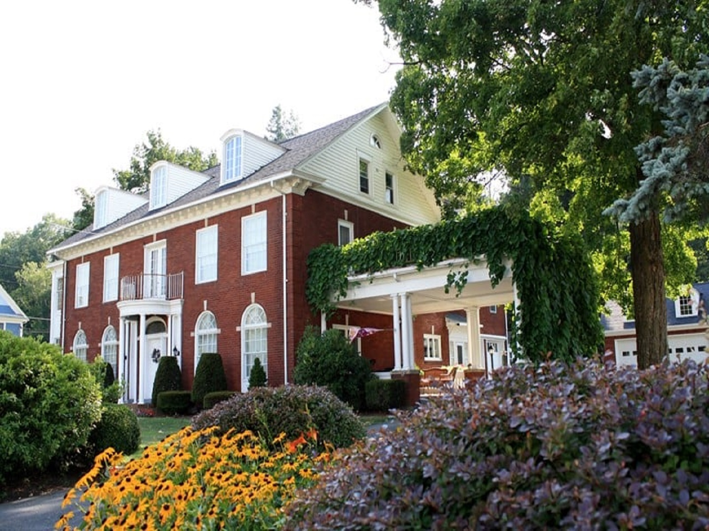 A house with bushes in front of a brick building at Mountain Laurel Bed & Breakfast.