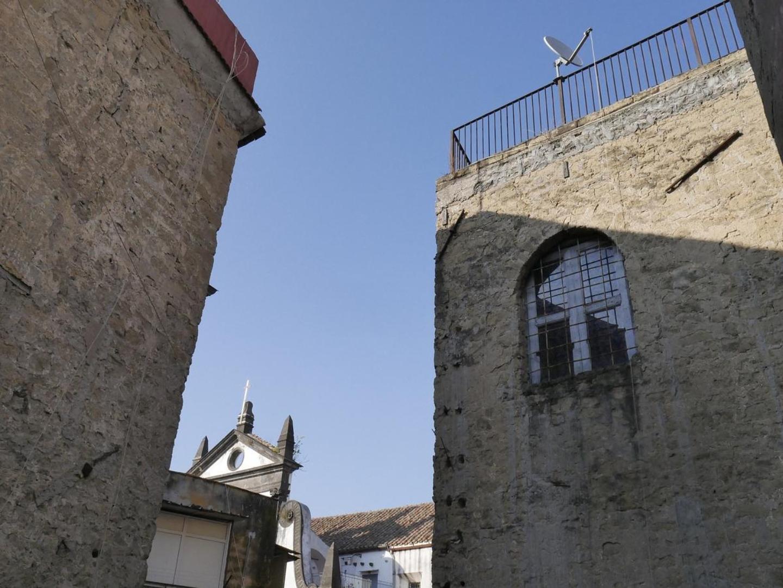 A large stone building with a clock tower at Casa Pesadina B&B.
