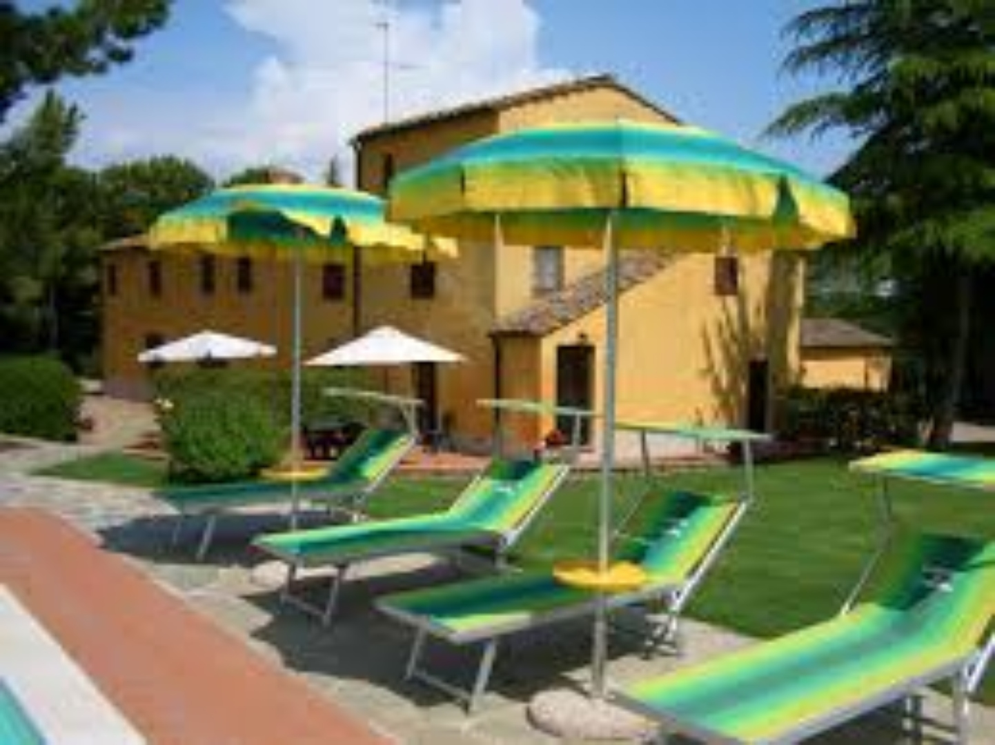 A group of lawn chairs sitting on top of a green umbrella at Casanova di Larniano.