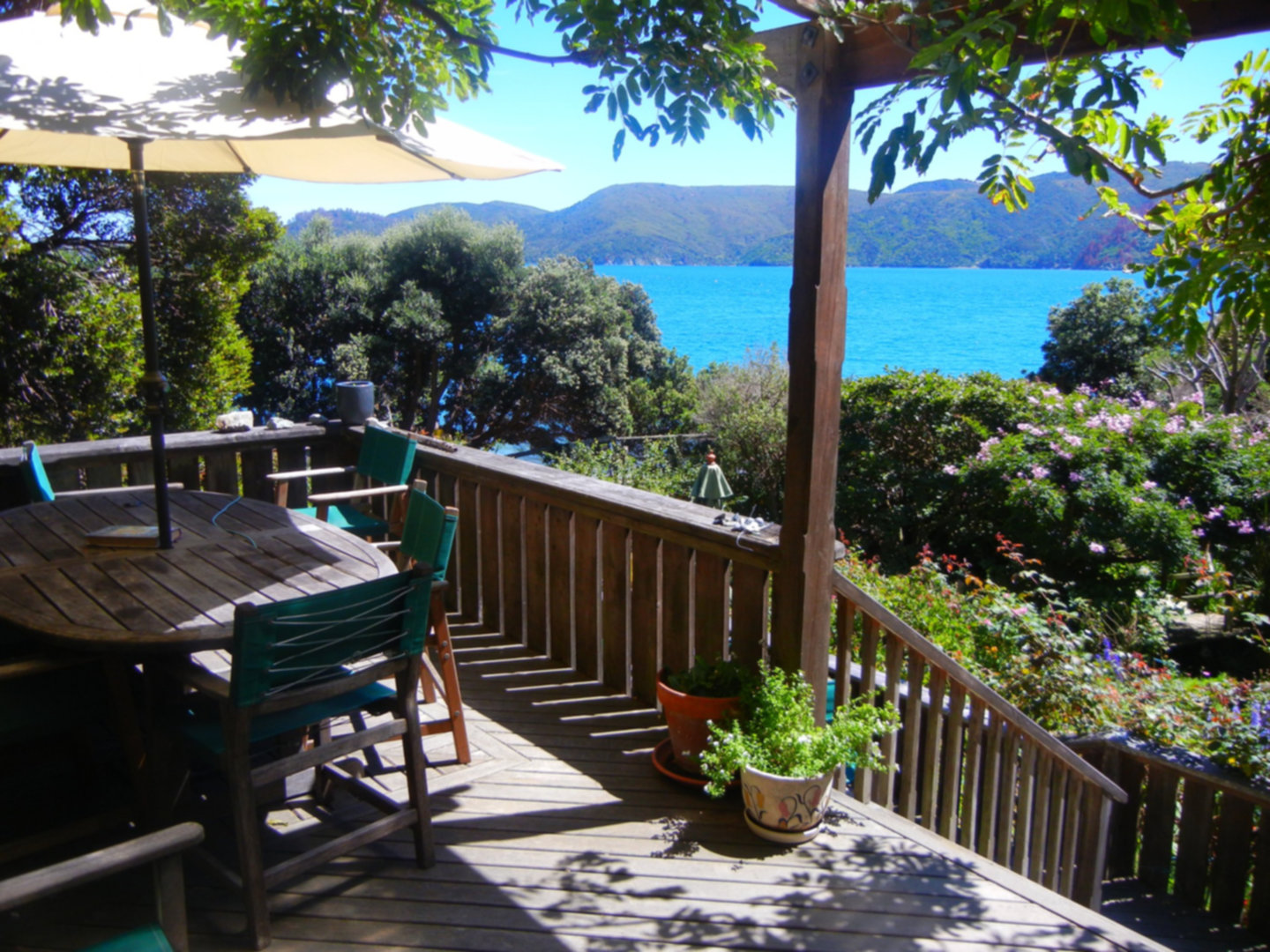 An umbrella sitting on top of a wooden table at Ngaio Bay.